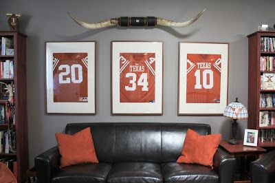 Classy Man Cave: Texas Longhorn-Themed Game Room Décor.  Framed retired Texas football jerseys, dark leather, and cherrywood stained furniture.  Click or visit FabEveryday.com for all the details on how to style your own chic (not tacky) man cave!