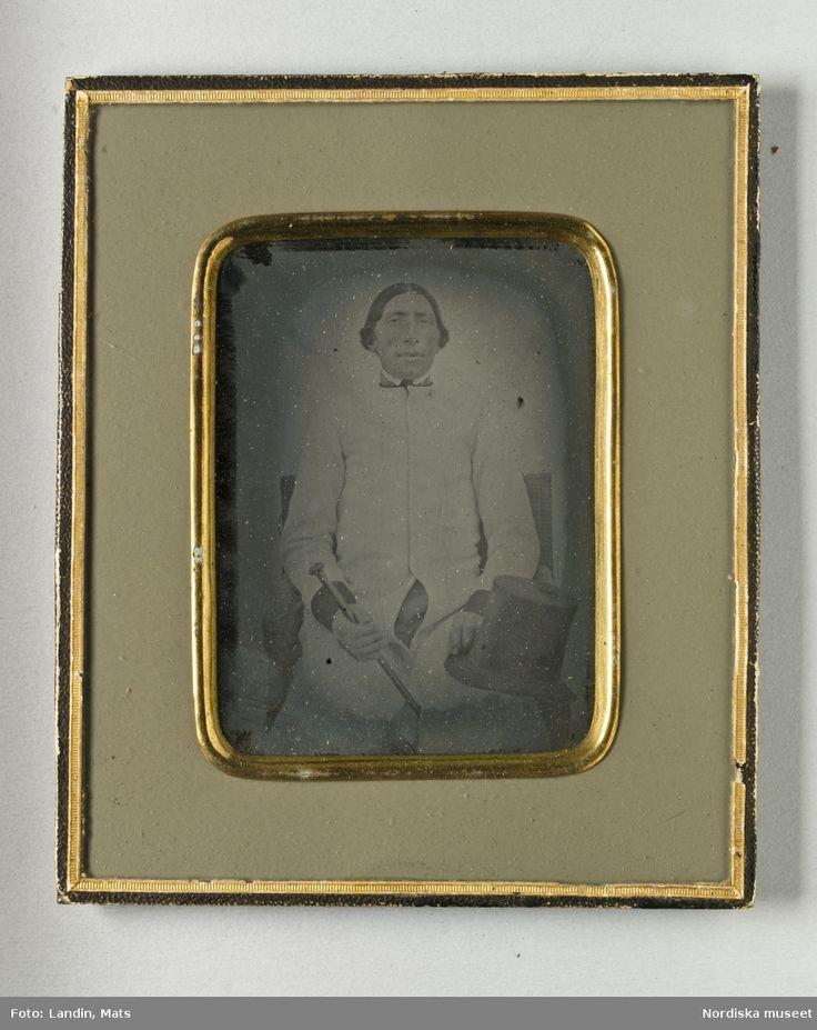 Porträtt av sittande man. Föreställer Lars Olsson från Västra Vingåkers socken, Oppunda härad, Södermanland. Mittbenat hår, iklädd ljus rock med mörka manschetter. I höger hand käpp. På vänster knä ligger hans höga hatt. Ambrotyp i ram Nordiska museet inv.nr 224538