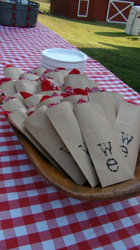 Stamped kraft paper bags with utensils and napkins tucked inside--super cute idea!!! BBQ/outdoor party ideas.