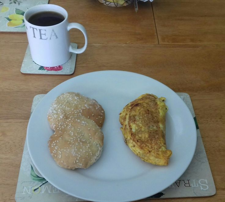Quick and easy breakfast; a stuffed omelette with black pudding and bacon lardons with two homemade sesame seeded buns with a cup of instant coffee