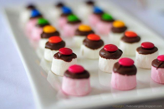 Doop marshmallows in gesmolten chocola en top af met m's. Klein en fijn, maar vooral leuk om te trakteren.