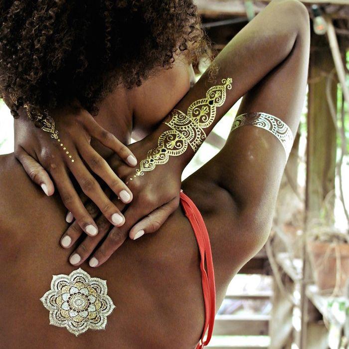 Металлические татуировки на загорелой коже.