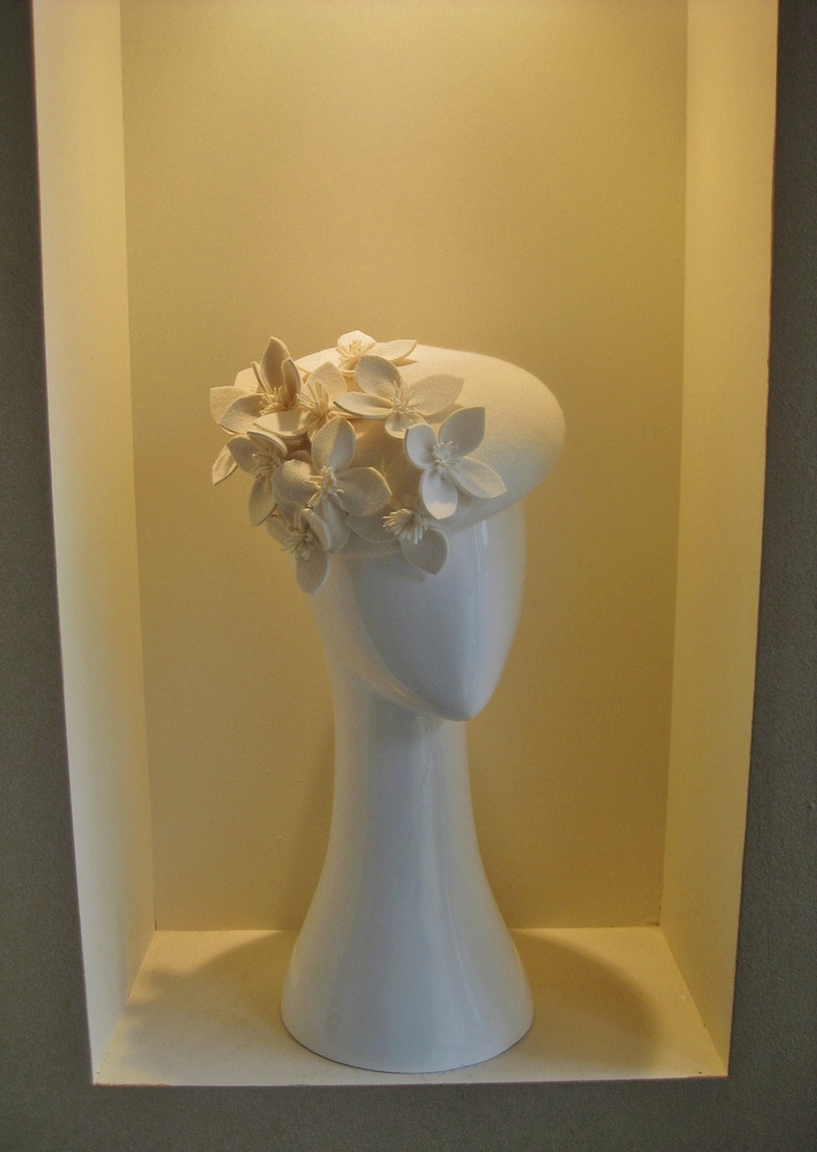 Winter white classic beret. A beautiful felt blocked beret that tips up the back to allow the wearer a ponytail or high bun. Adorned with flowers that each petal has been hand cut, hand sewn and stitched in place for perfect balance. A great autumn raceday classic