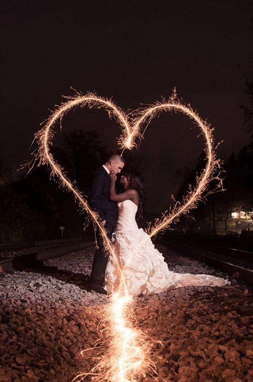 A couple is framed in a heart created with sparklers.
