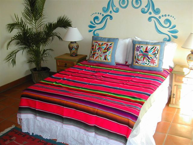 "Painted ""headboard"" and embroidered pillows for a colorful, casual Mexican bedroom."