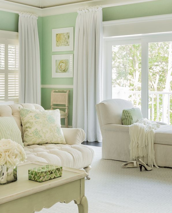 Stunning ivory and mint green bedroom features mint green walls adorned with white chair rail trim alongside window and sliding patio doors dressed in white floor length drapes.