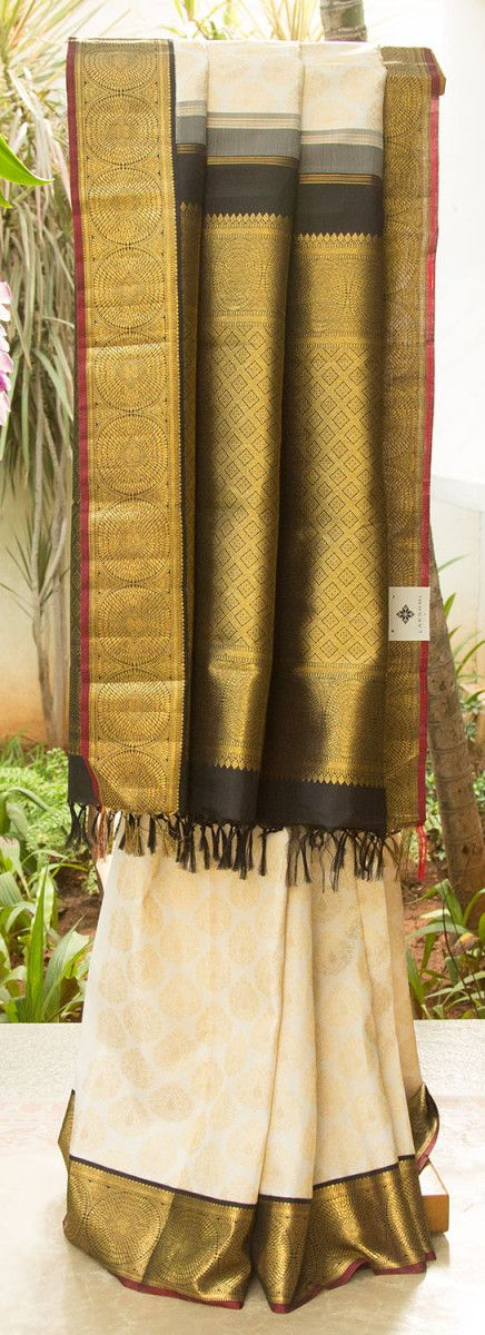 A majestic white kanchivaram silk with beautiful floral zari motifsall over the body. An intricate and uniform zari pattern on the contrasting black border brings the sari to life. A classy and fi...