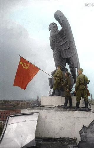 Soviet soldiers hoisting the Soviet flag in Berlin, German. World War II, 1945.
