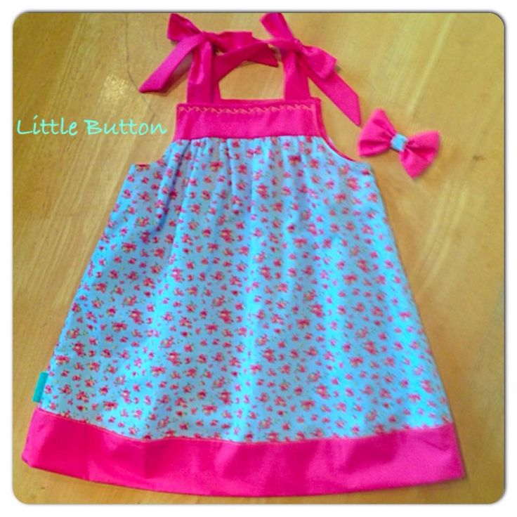 Blue ditsy floral fabric sundress with shocking pink hem and straps, matching hair bow.
