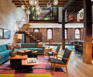 El gran espacio abierto en el primer piso de la vivienda utiliza algunas de las vigas de madera y ladrillo visto dejados por la historia del edificio.  Sin embargo, también añade magníficos pisos de madera y un montón de notas de color, incluyendo un sofá verde azulado impresionante y mesa de centro modular creativo.