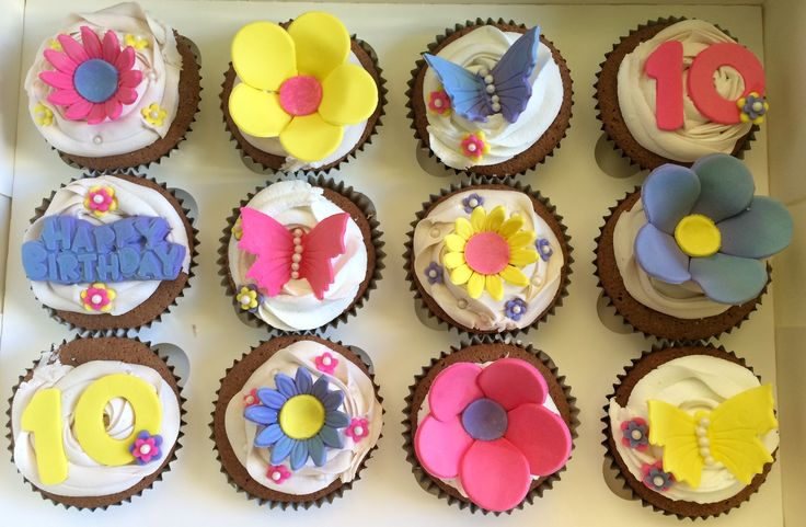 White frosting and pink/purple and yellow butterflies and flowers. Birthday cupcakes! So pretty! Check out my page https://www.facebook.com/frosted.cupcakes.invercargill/