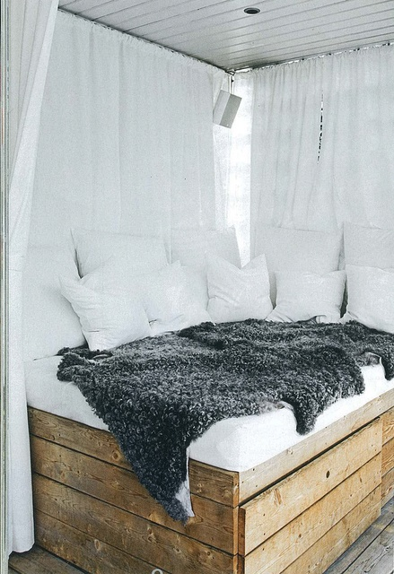 Reclaimed, rough hewn wood paired with crisp white fabric makes for a chic and inviting daybed.