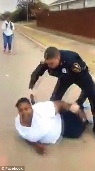 After the scuffle, the officer wrestles Craig to the ground and presses a Taser to her back (above)