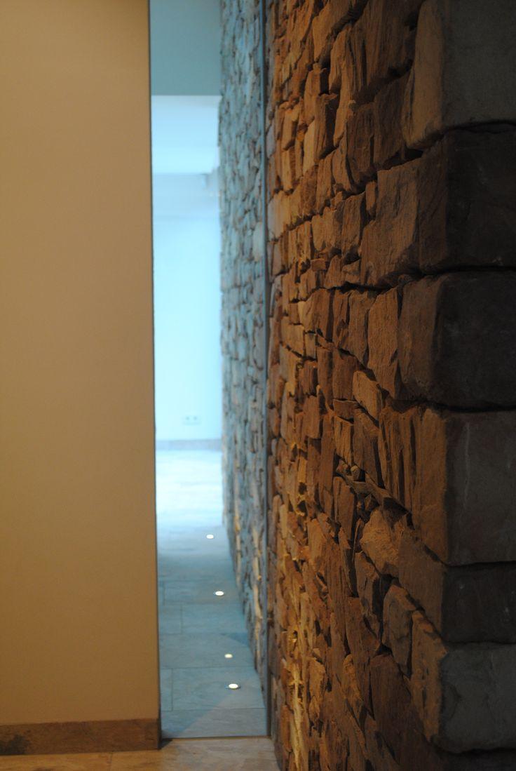Doorkijk van overloop naar wellness ruimte. Met glasstrook van vloer tot plafond en vloerspots. De wand gemaakt door Bonte maatwerkstenen maken het geheel af.