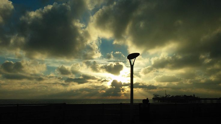 The Sun going down illuminates Brighton Pier, UK.