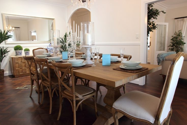 A Hamptons style dining room with cross back chairs and linen end chairs to…