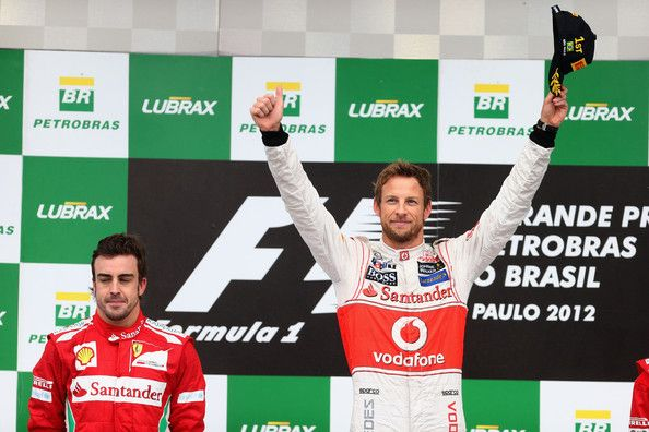 Race winner Jenson Button (R) of Great Britain and McLaren and second placed Fernando Alonso (L) of Spain and Ferrari celebrate on the podium