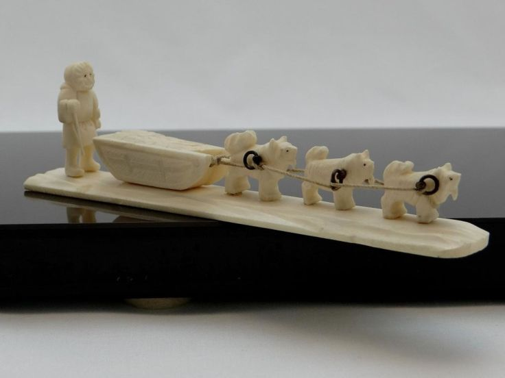 Os de morse sculpté, esquimau et traîneau, travail Inuit 1950  Ravissante sculpture Inuit des années 1930/1950 en os de morse figurant un esquimau et son traîneau tiré par trois chiens.  Travail d'une grande finesse. Superbe objet de charme et de vitrine. Alaska ou Canada, ethnie Inuit, années 1950/1960.  Longueur 15 cm.Bon état, petite fente sur la jambe gauche, sans incidence.