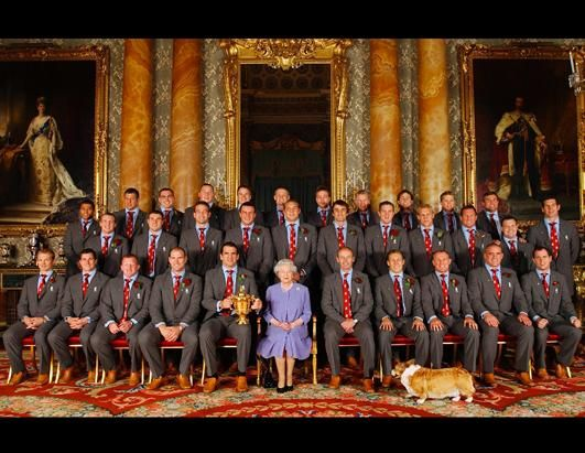 """Queen Elizabeth II with one of her corgis and the England Rugby Squad at Buckingham Palace to celebrate the Rugby World Cup win in 2003. The Palace called upon Mugford again this summer when there was yet another corgi conflagration. His solution for fighting dogs is a can of """"hissing spray"""" -- perhaps that is what the queen carries in her purse."""