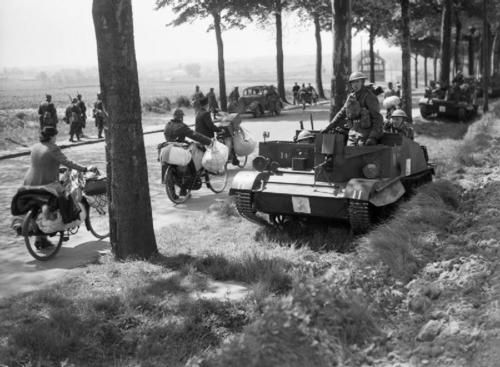 Bren gun carriers pass Belgian refugees on the Brussels-Louvain road, 12 May 1940.