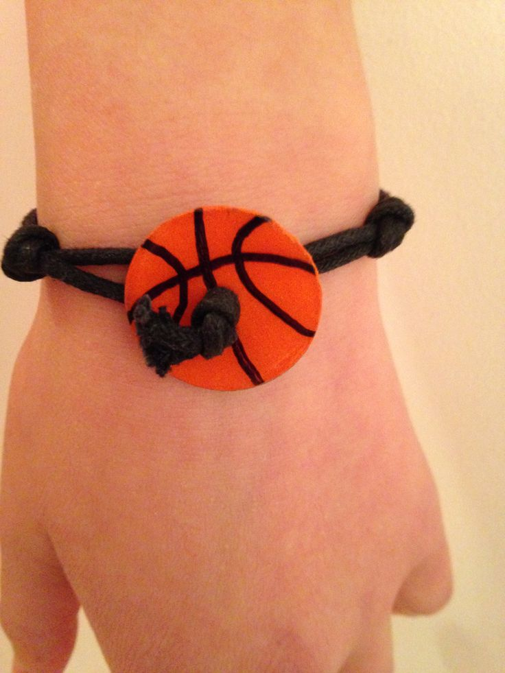 """Basketball bracelet:  1"""" washer, orange scrapbook paper, Sharpie, ModPodge regular and Dimensional Magic.  Thin paracord (#95) threaded through middle, knotted and other end is a loops that fits over the washer, like a button hole.   Side knot made to offset visual of button-hole knot."""