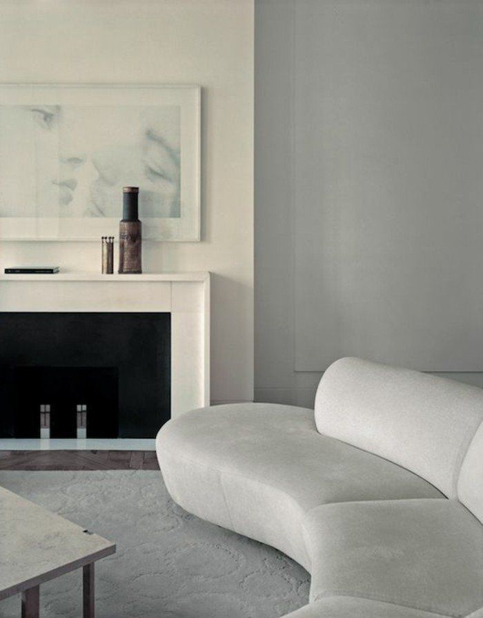 canapé d'angle arrondi de couleur blanc dans le salon chic avec chminée d'intérieur