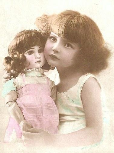 Petite fille et sa poupée vintage. Ancienne photographie.