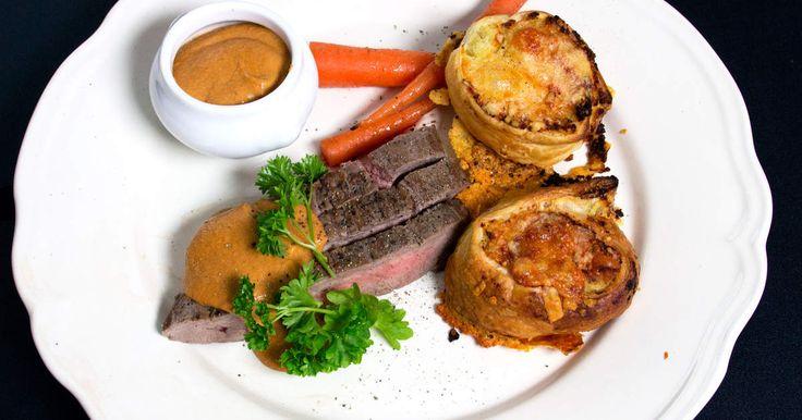 Flankstek serverad med potatispuckar gratinerade med västerbottensost, en gräddig sås och rostade morötter.
