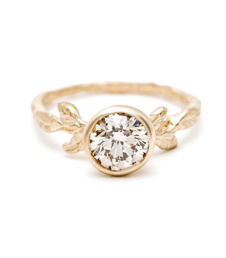 Whimsical and organic,this beautiful 14K yellow gold ring is highlighted with a brilliant cut champagnediamond (1.00ct). Textured leaves and a twig band add to the rustic, nature-inspired charm of the piece. We love this ring choice for a non-traditional, bohemian engagement ring or the centerpiece on a stacked set. A brilliant gift for a nature loving woman with a flair for unique, hand-crafted design.Shown with a round brilliant cut champagne diamondcenter, this ring is also available…