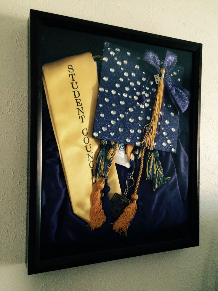 Shadow box of high school graduation cap and gown