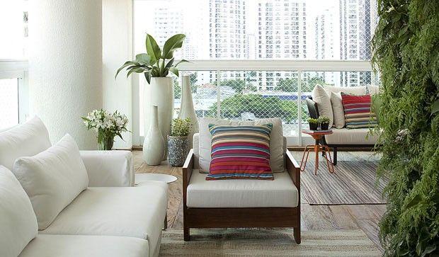 Varanda em tons claros, com jardim vertical, vasos de planta e almofadas coloridas