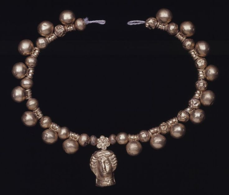 DescriptionGold necklace composed of: a) seventeen vase-shaped pendants with movable stoppers; b) nineteen plain hollow beads; c) two smaller plain hollow beads; d) central pendant in the form of a female head, wearing a necklace and crescent-shaped pendant; the suspending cylinder is masked by a double rosette. More  Culture/period    Etruscan term details Date   400BC-300BC