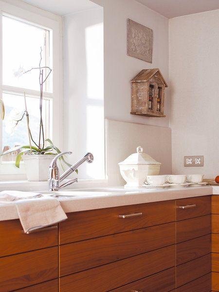 cocina en blanco y madera con fregadero delante de la ventana