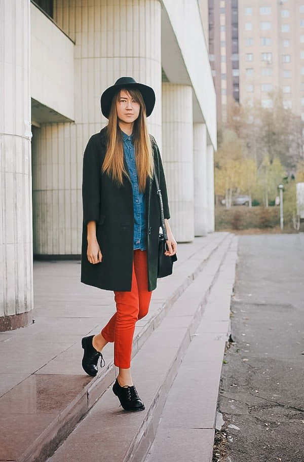 Perfect the smart casual look in a hunter green coat and red fitted pants. Complement this look with black leather oxford shoes.  Shop this look for $116:  http://lookastic.com/women/looks/hat-denim-shirt-skinny-pants-oxford-shoes-satchel-bag-coat/5336  — Black Wool Hat  — Blue Denim Shirt  — Red Skinny Pants  — Black Leather Oxford Shoes  — Black Leather Satchel Bag  — Dark Green Coat