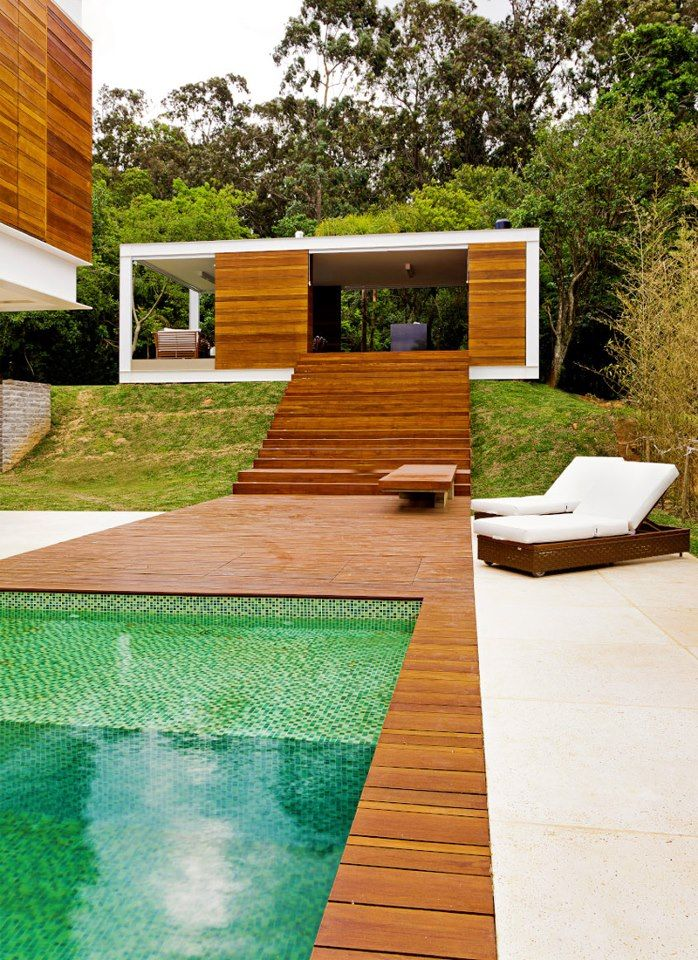 modern pool. luxe, tobacco-colored decking, shipping container cabana idea. green tiles.