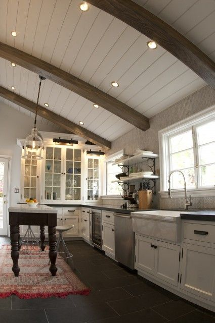 Country kitchen featuring an arched barrel ceiling with exposed wood beams and recessed lighting, and a dark, slate-tiled floor