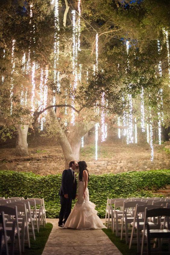 Confira 10 ideias de iluminação para casamentos ao ar livre. Luzes caem de árvore em casamento no campo ao ar livre. Noivos após cerimônia de casamento em jardim se beijam e transformam o ambientes de casamento. As ideias de decoração e iluminação de casamento são essenciais e fazem a diferença em festas.