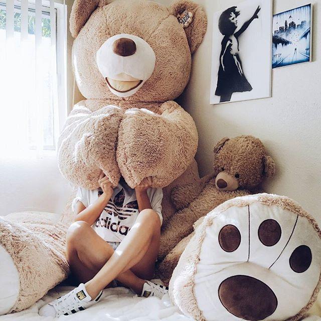 Chica abrazando un oso gigante de peluche