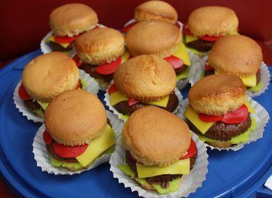 een hamburger van chocolade cake tussen twee halve cupcakes, sla tomaat en kaas zijn van marsepein