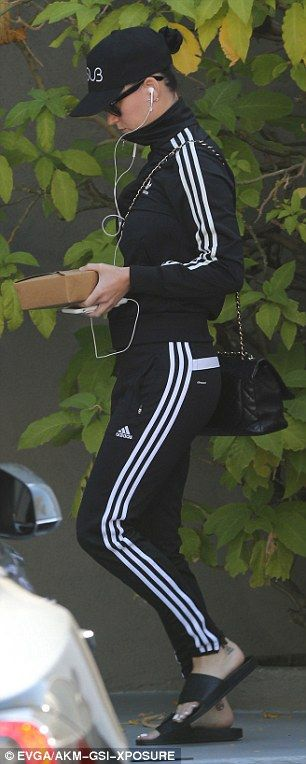 Quick escape: She was seen leaving her office in a black baseball cap, a black Adidas tracksuit and black sandals