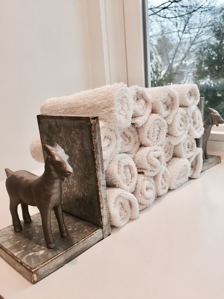 Two goat bookends serve as towel holders in this beautiful traditional bathroom with a Scandinavian feel.