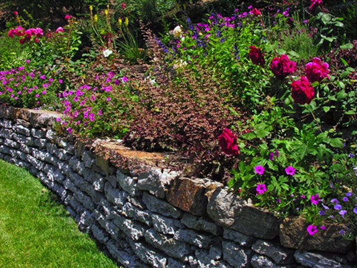 Onsite recycling creates a retaining wall for a lovely perennial garden.  You can spray iron oxide with water to stain the face for a more natural look.