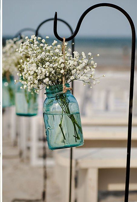 Antique blue mason jars with baby's breath on shepherd hooks along aisle, beach wedding