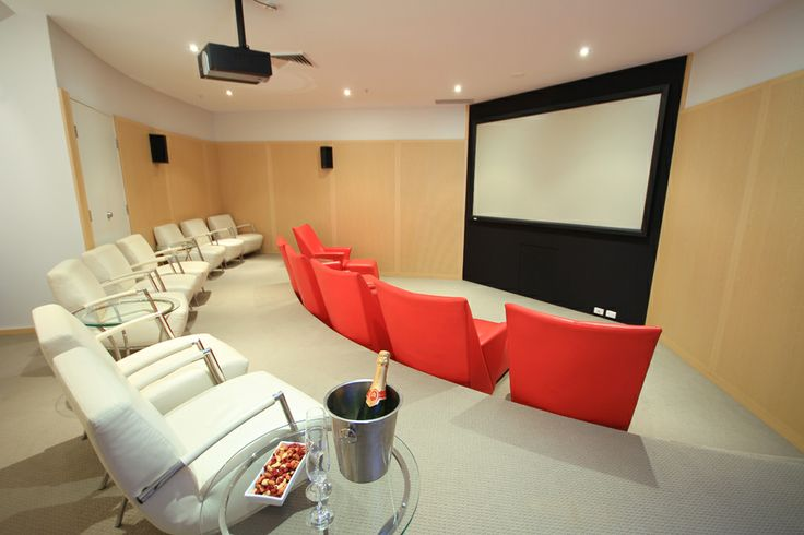 Oceans Mooloolaba theatrette with mounted projector, fixed frame screen and integrated wall speakers, all controlled by a wall mounted colour touch screen. With seating for 14 people in leather chairs with ottomans and contemporary accent tables, this private cinema is available for hire by guests or professional presentations.