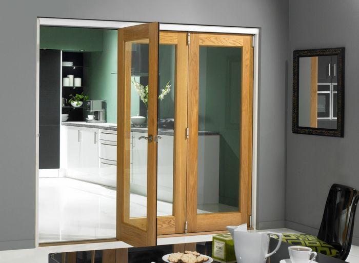 schiebetür küche harmonikatür glas holz grüne wand schwarzer esstisch spiegel schwarzer plastikstuhl