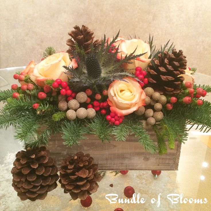 A jolly holly arrangement with roses, silver brunia, blue thistles, red berries and pine cones.