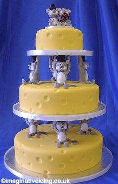 Mice and Cheese (143)    Round cakes decorated to look like cheeses. Special supports are decorated to resemble comical mice in top hats with their arms above their heads as though supporting the tiers.