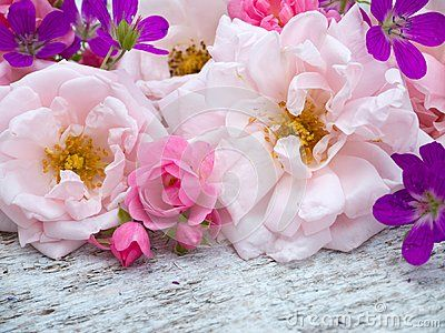 Large pale pink and small bright pink roses and geranium bouquet on the white rough wooden table