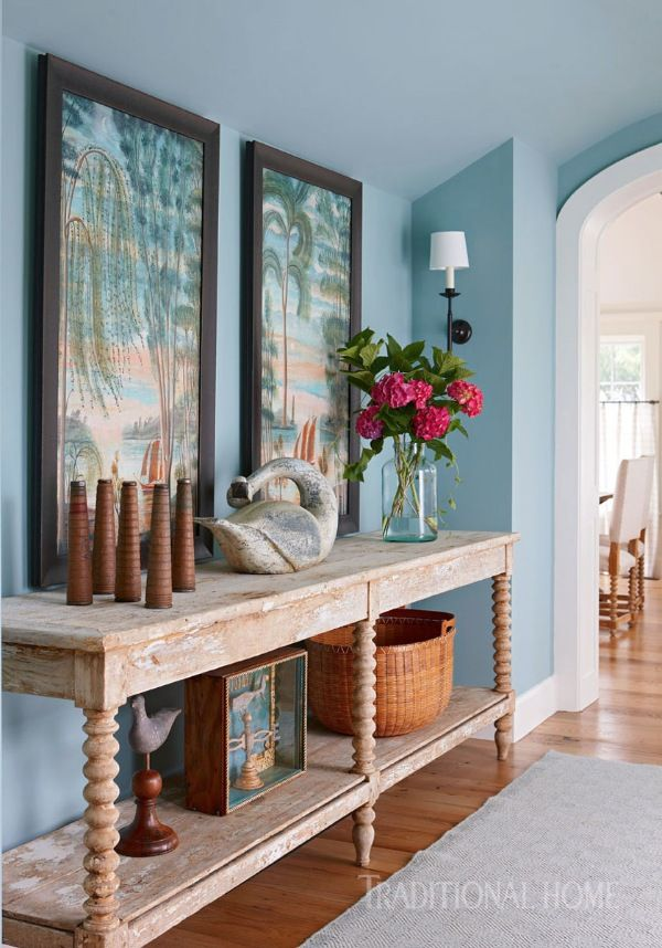 "Farrow & Ball's ""Dix Blue"" distinguishes the entry hall, where an antique French laundry table settles beneath paintings by Kevin Paulsen. - Photo: Michael Partenio / Design: Nancy Serafini"