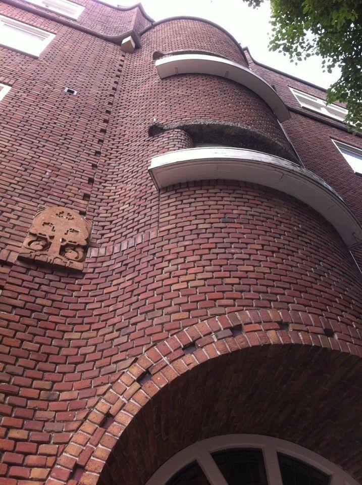 Amsterdamse school bouwstijl. Rondingen ladderramen verschillende steensverbanden en torentjes afwijkende houtwerken. De typische kenmerken.